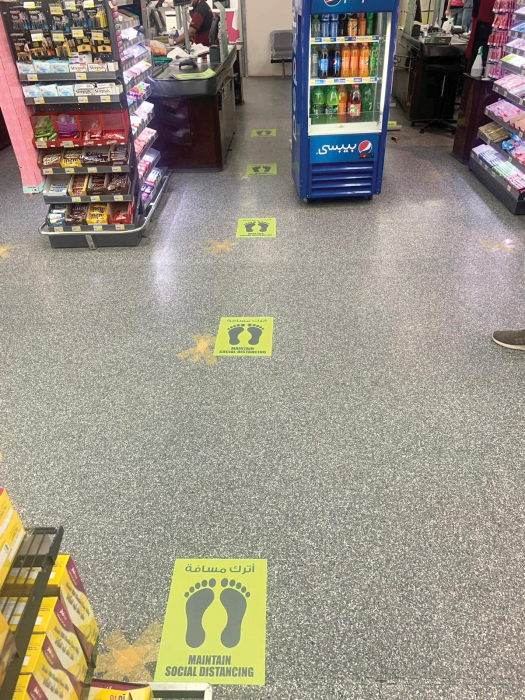 Image of floor stickers in a grocery store marking how far apart one should stand when waiting for the cashier