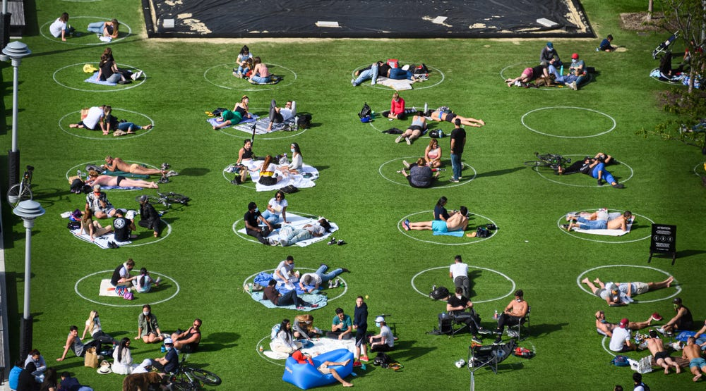 Photo of an outdoor lawn space in New York with white circles drawn on the ground and people relaxing within them.
